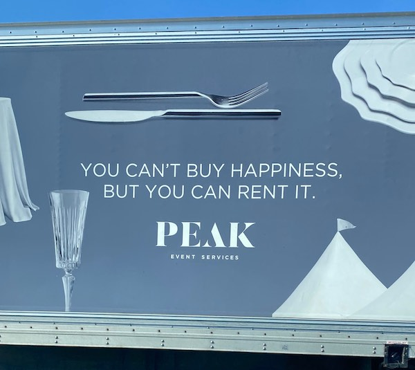 """A truck with the slogan """"You can't buy happiness, but you can rent it."""" on it."""