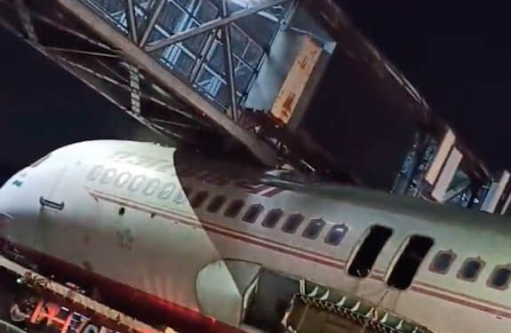 A plane wedged under a bridge or other structure.
